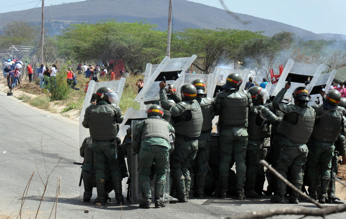 Members of the National Guard take shelter before a riot in front of the prison Uribana, in Barquisimeto, Lara state, Venezue