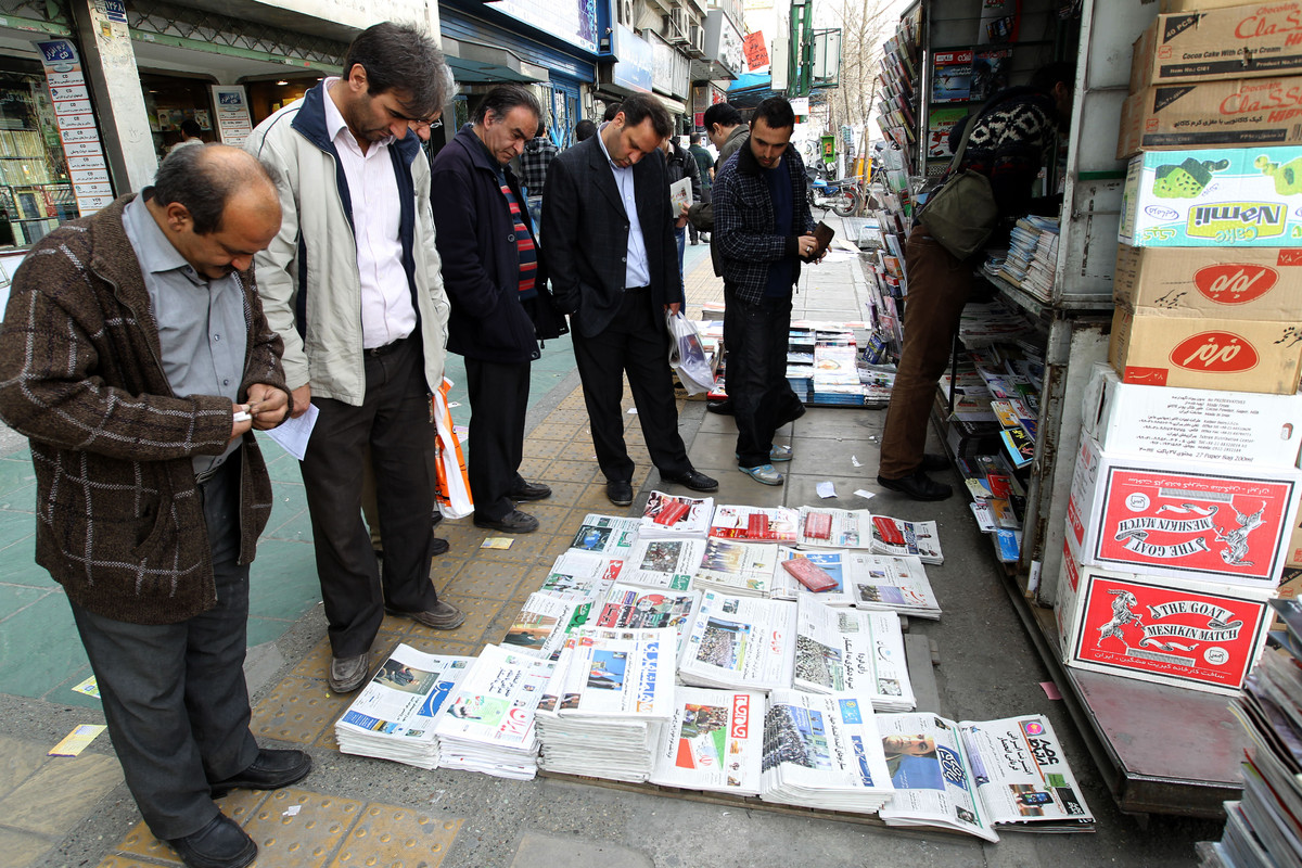 Iranian men look at newspapers displayed at a kiosk in central Tehran on March 1, 2012 on the eve of a parliamentary election
