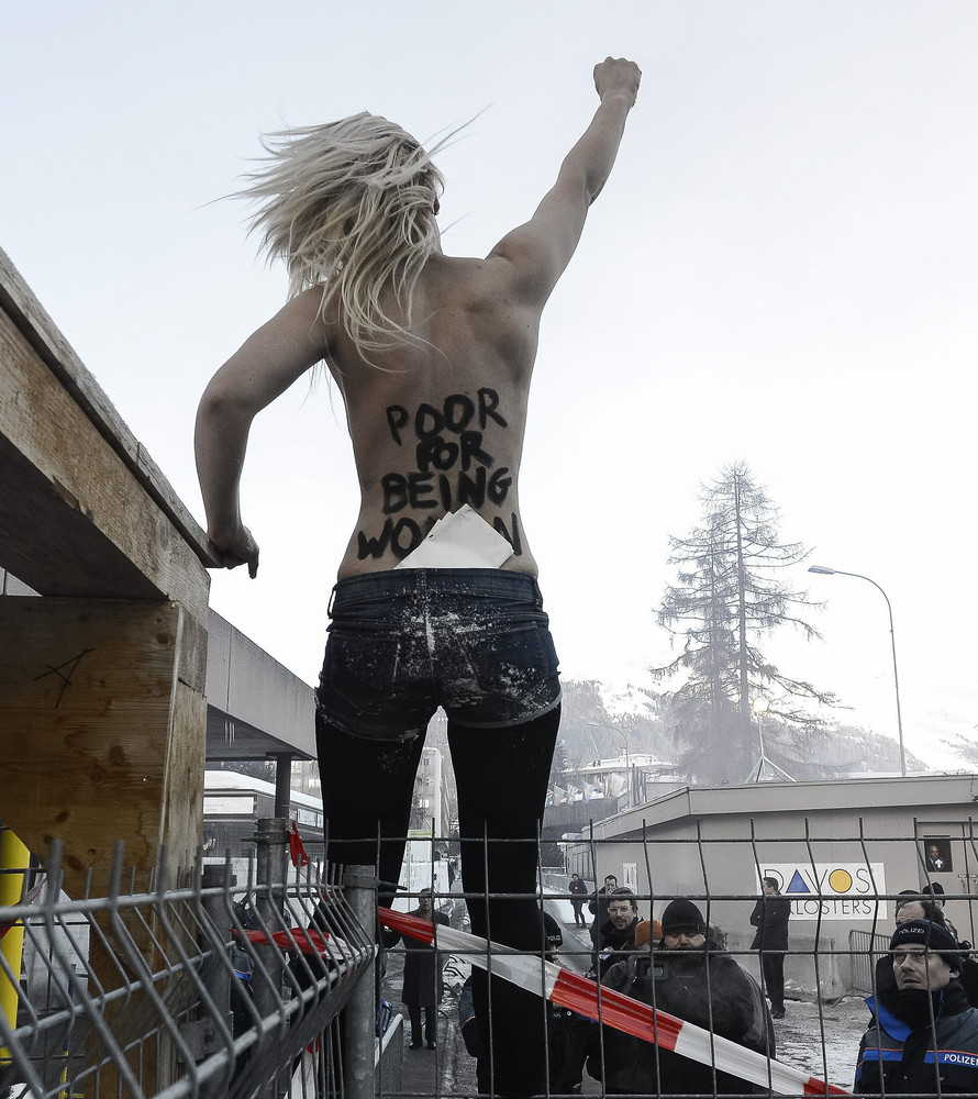 An activist of the Ukrainian feminist group FEMEN stands on a fence during a protest at the 43rd Annual Meeting of the World