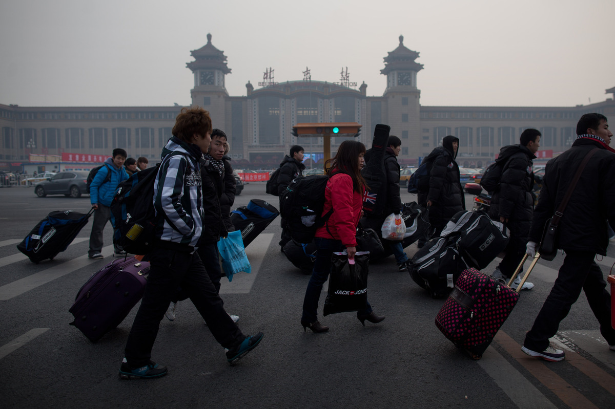 Travelers cross a road before Beijing Railway Station in Beijing. (Ed Jones/AFP/Getty Images)