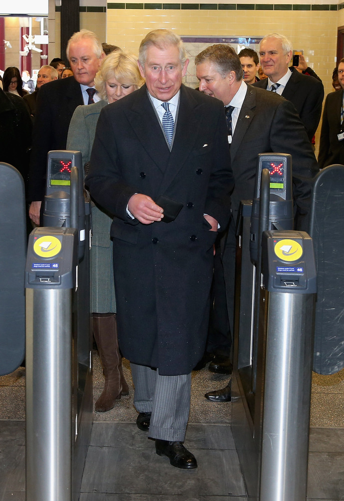 Prince Charles, Prince of Wales and Camilla, Duchess of Cornwall walk through a ticket gate as they prepare to travel on a Me
