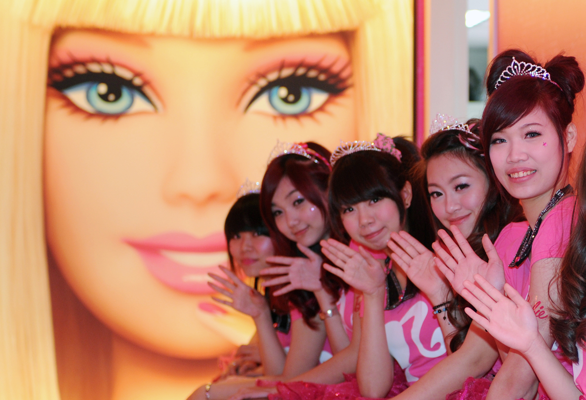 Waitresses wave in front of a Barbie poster during the opening ceremony of a Barbie-themed restaurant in Taipei on January 30