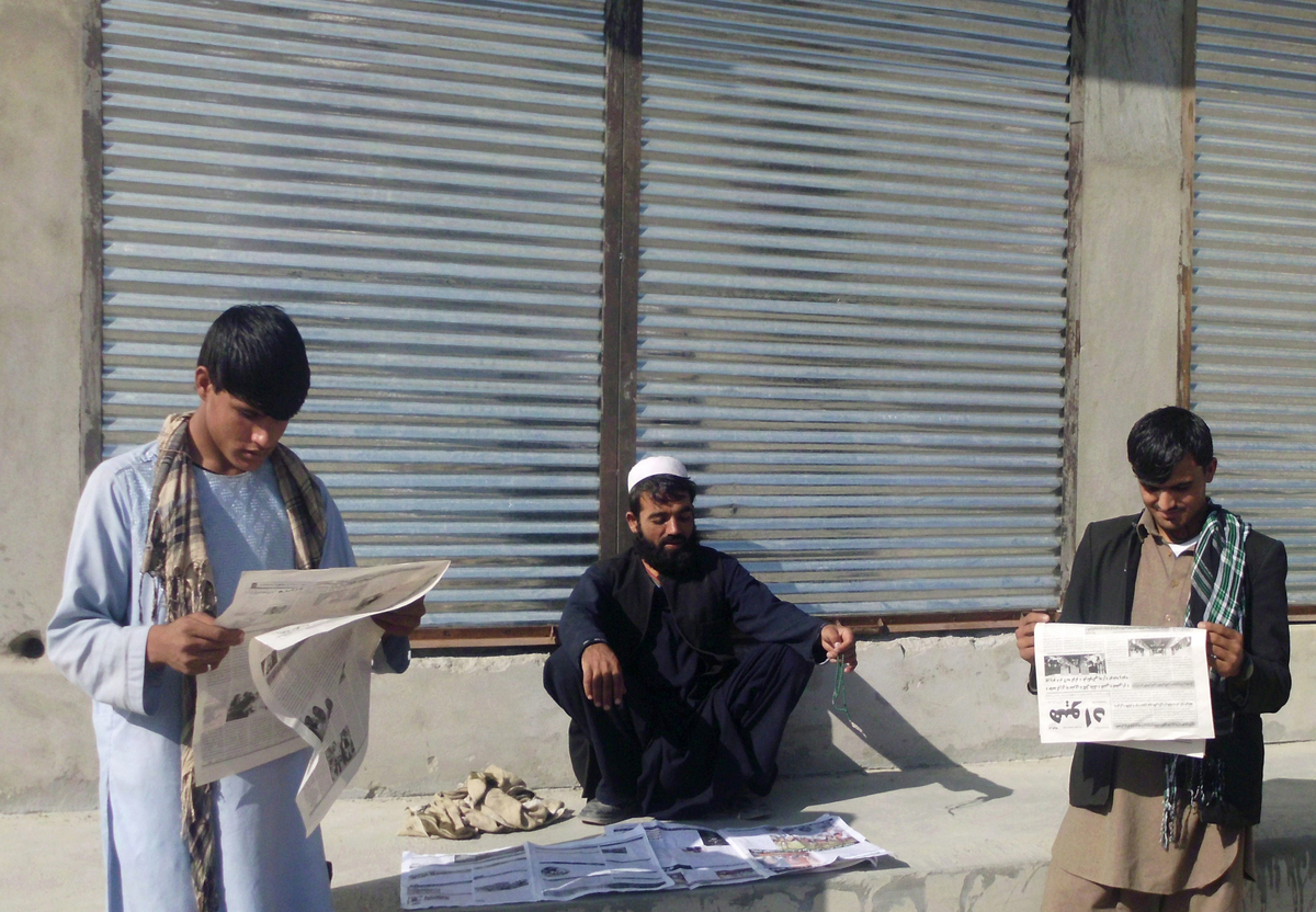 Afghan men read newspapers in Laghman province on November 10, 2012. Afghanistan's media sector has boomed in the last decade