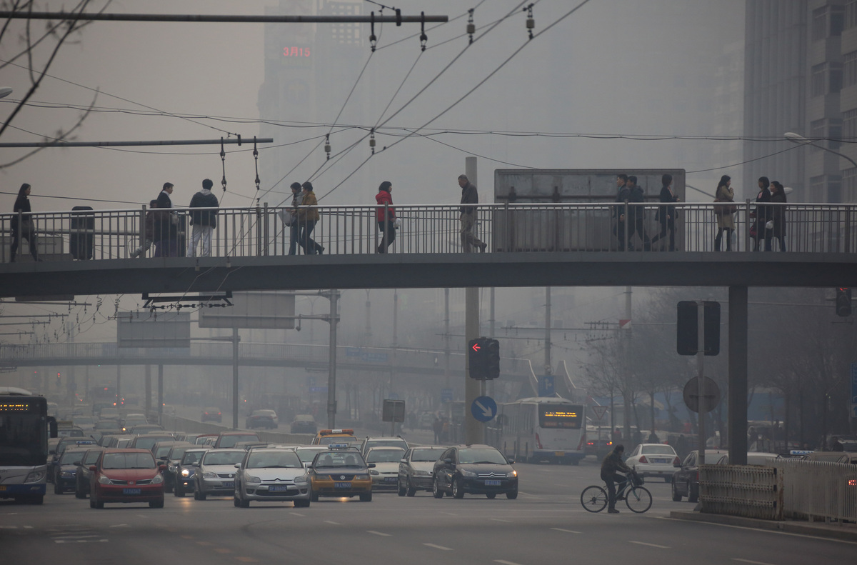 Traffic moves along a street as pedestrians walk on an overpass shrouded in haze in Beijing, China, on Friday, March 15, 2013
