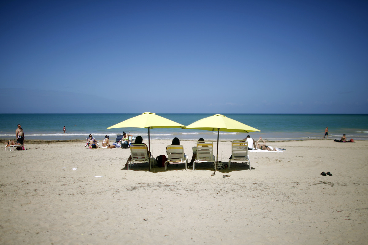 People enjoy a sunny day at the Isla Verde Beach, in Carolina, Puerto Rico, Jan. 24, 2013. A good tip for all Puerto Rican be