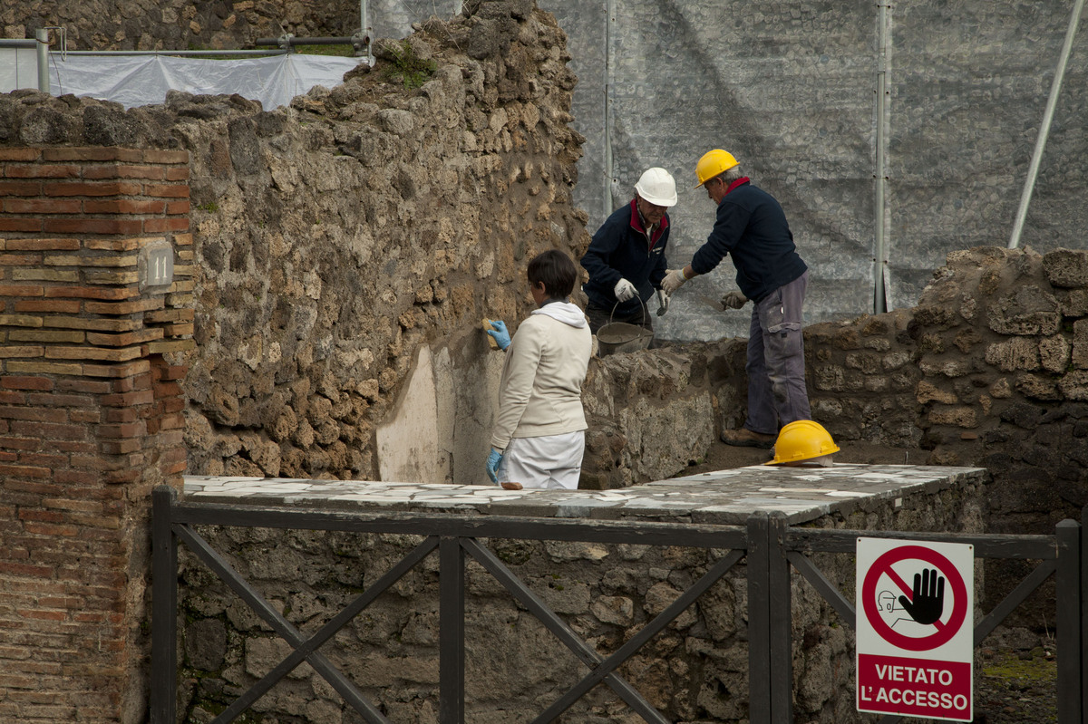 Restoration employees work on an archeological site on February 6, 2013 in Pompeii. An ambitious restoration project dubbed '