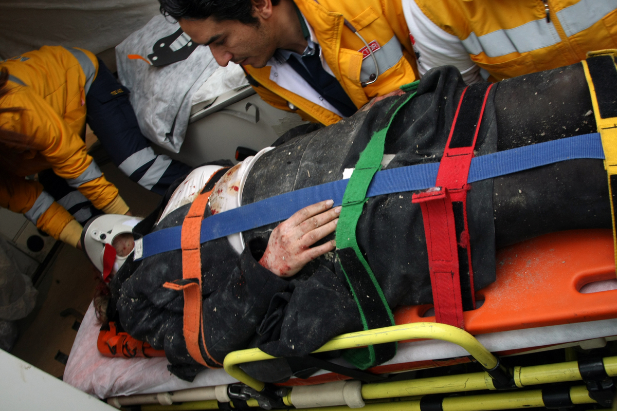 Medics and firefighters carry an injured woman on a stretcher to an ambulances after a suicide bomber had detonated an explos