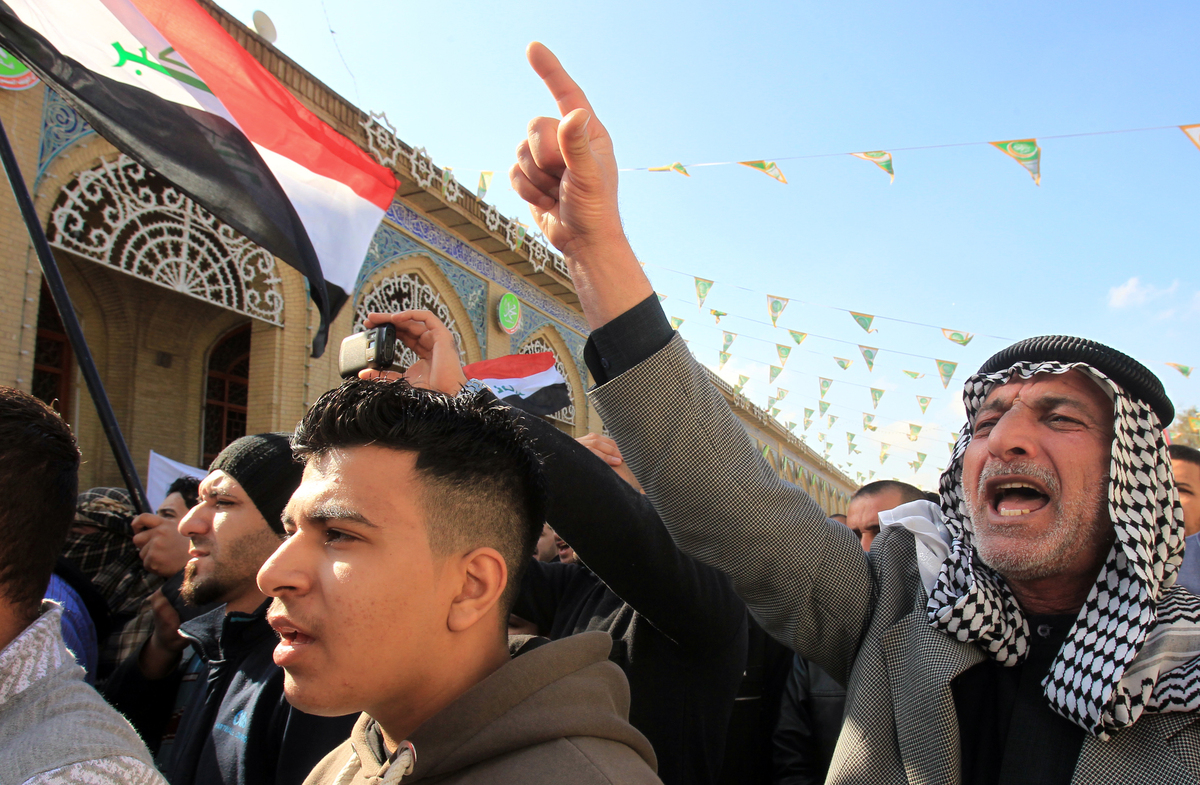 Sunni Muslims shout slogans during an anti-government demonstration outside the Sunni Abu Hanifa mosque in Baghdad's Adhamiya