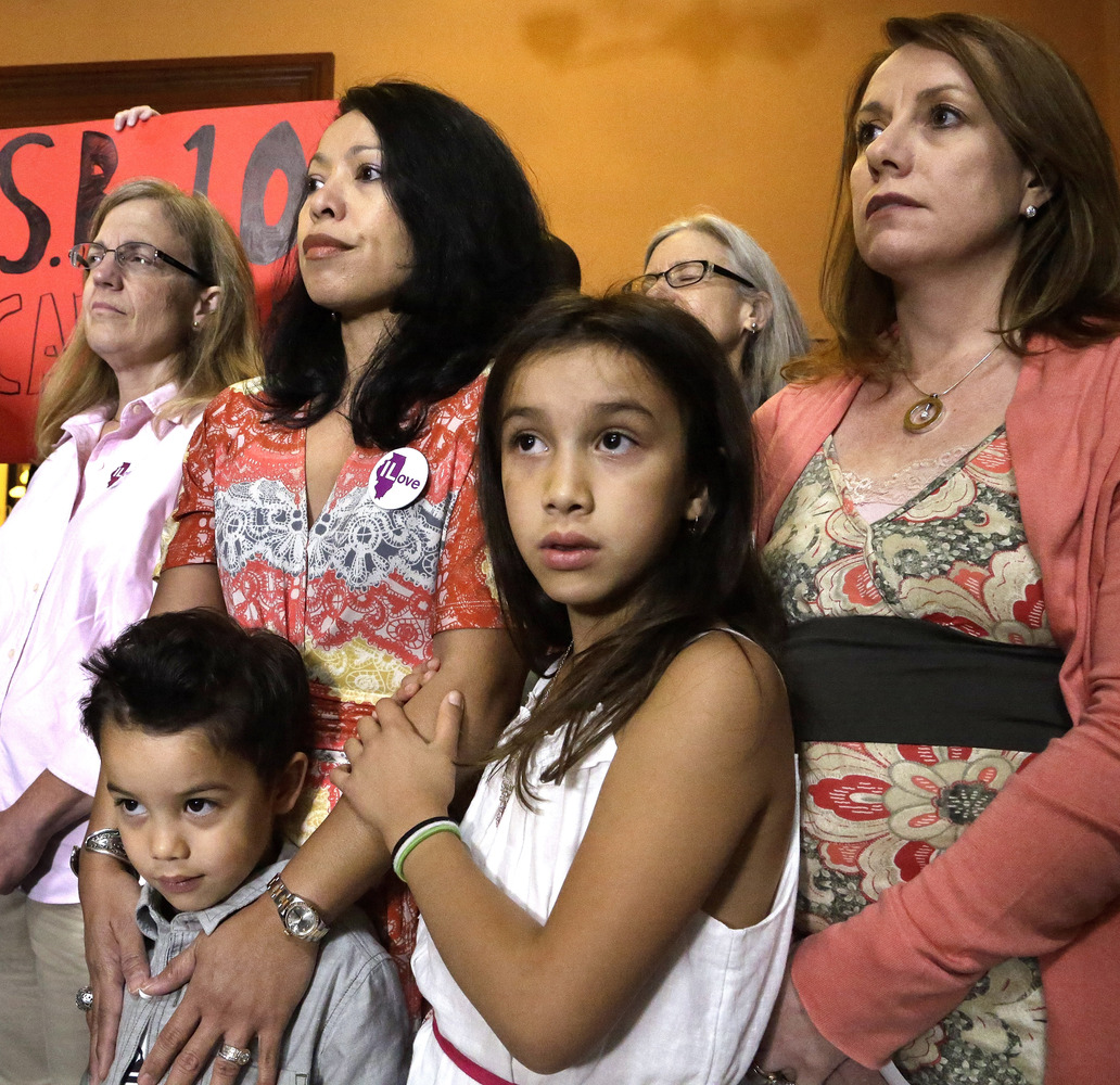 Theresa Volpe, right, stands alongside her daughter Ava as her partner Mercedes Santos, left, holds their son Jaidon outside