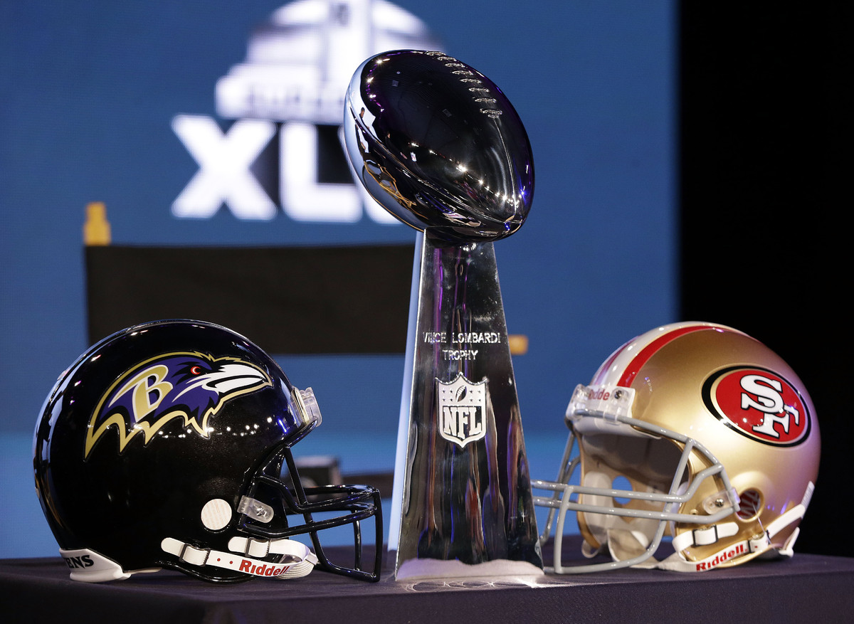 The Vince Lombardi trophy is displayed before and San Francisco 49ers head coach Jim Harbaugh and Baltimore Ravens head coach