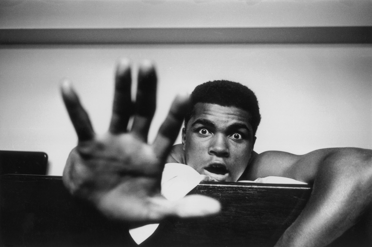Cassius Clay at his hotel in London on 27 May 1963 holding up five fingers predicting how many rounds it will take to KO Henr