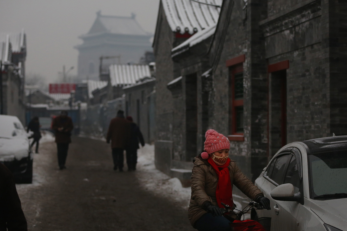 A woman wearing a mask rides through an alley near the Bell Tower during severe pollution on February 3, 2013 in Beijing, Chi