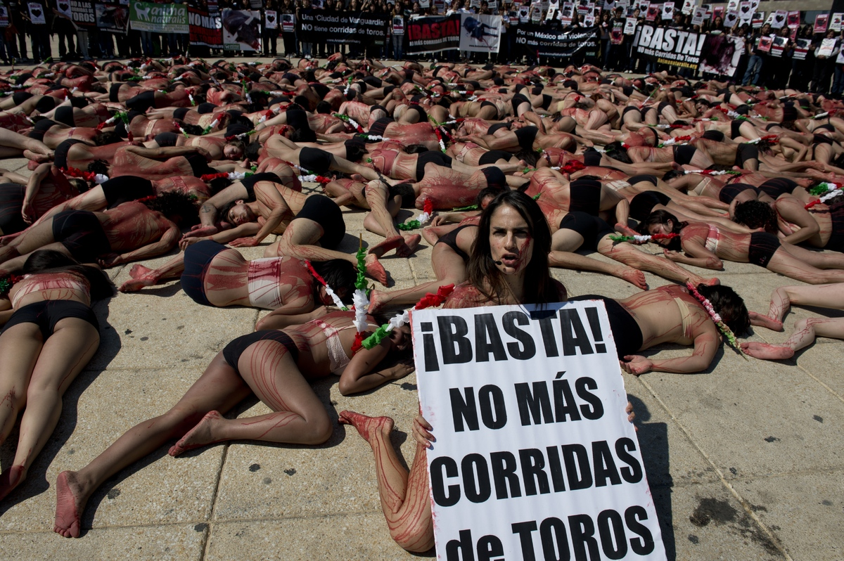 Activists members of Animal Naturalis organization perform during a protest against bullfighting, at the Revolution monument