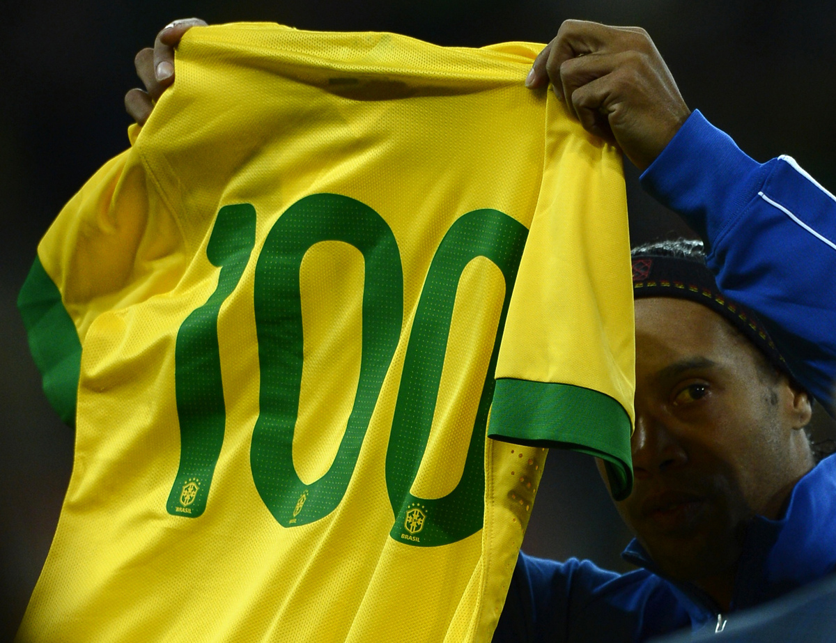 Brazil's midfielder Ronaldinho (R) holds a Brazil shirt printed with '100' awarded to him to commemorate his hundredth appear
