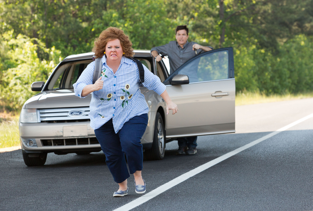 This undated publicity image released by Universal Pictures shows Jason Bateman, background, and Melissa McCarthy in a scene