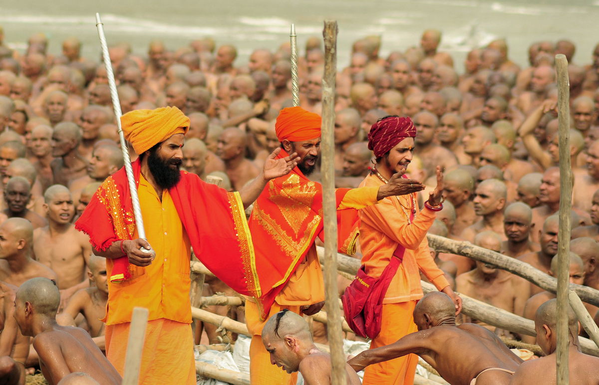 Members of Juna Akhara (Kotawal) discipline newly initiated 'naga sadhus' as they perform rituals on the banks of the Ganga R