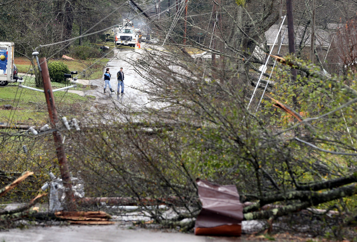 A couple cross West Arlington Loop in Hattiesburg, Miss., Monday, Feb. 11, 2013, after a tornado damaged the area Sunday afte