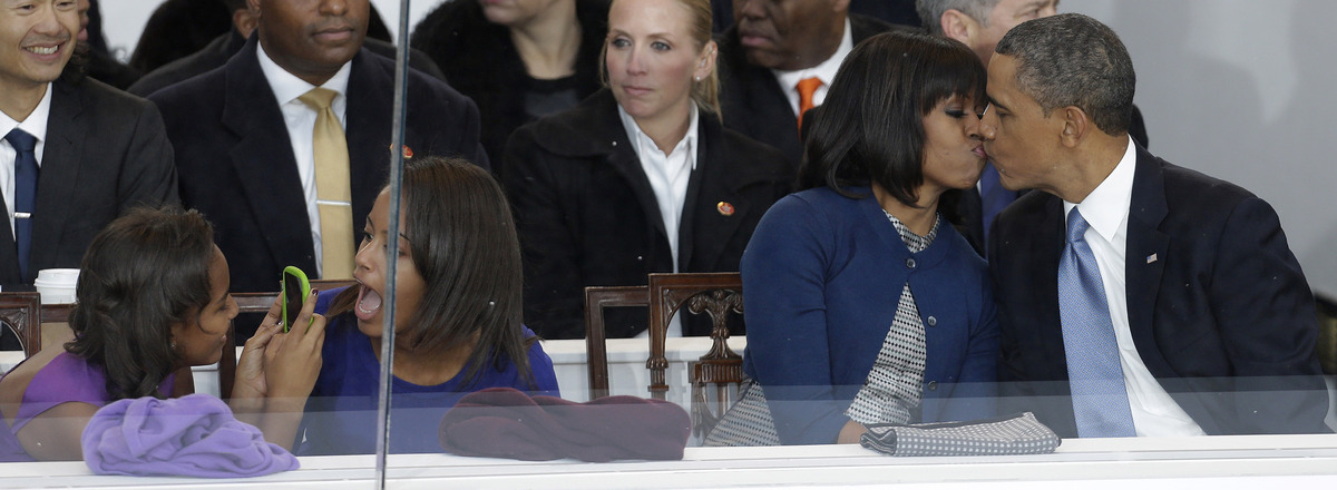President Barack Obama kisses first lady Michelle Obama as their daughters Sasha, left, and Malia, second from left, look on