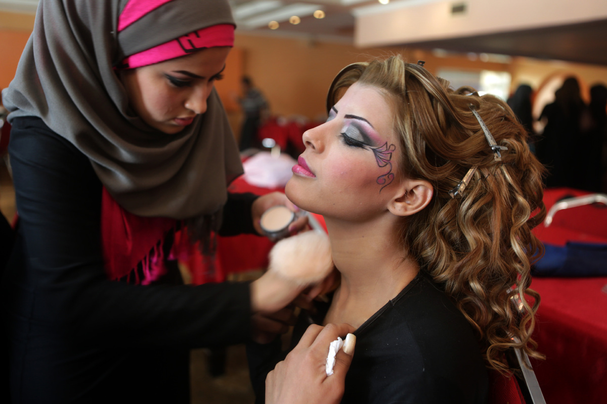 An Iraqi model is made up backstage before a show during a hairdressers and make up artists festival on February 9, 2013 in B