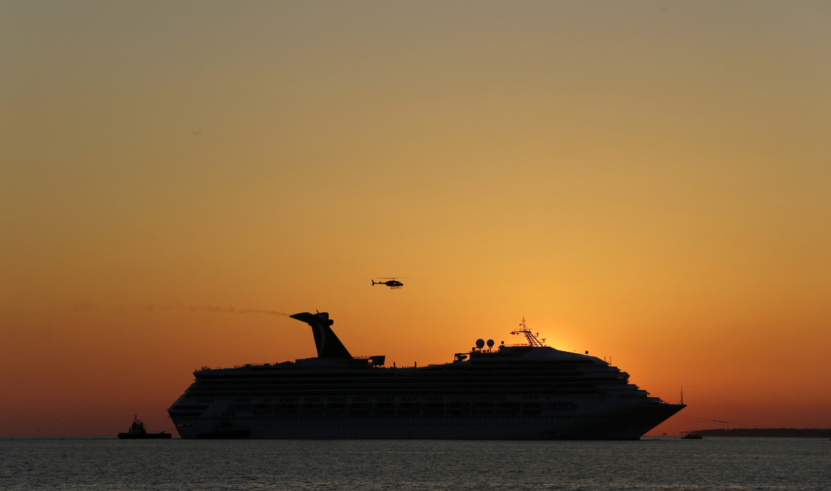 The sun sets as the cruise ship Carnival Triumph is towed into Mobile Bay near Dauphin Island, Ala., Thursday, Feb. 14, 2013.