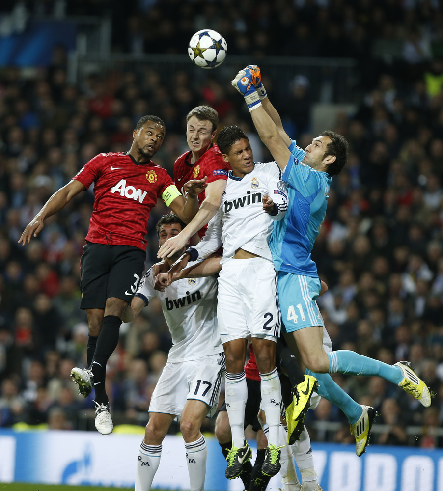 Manchester United's Patrice Evra, left, and Jonny Evans contest a high ball with Real Madrid's Raphael Varane from France and