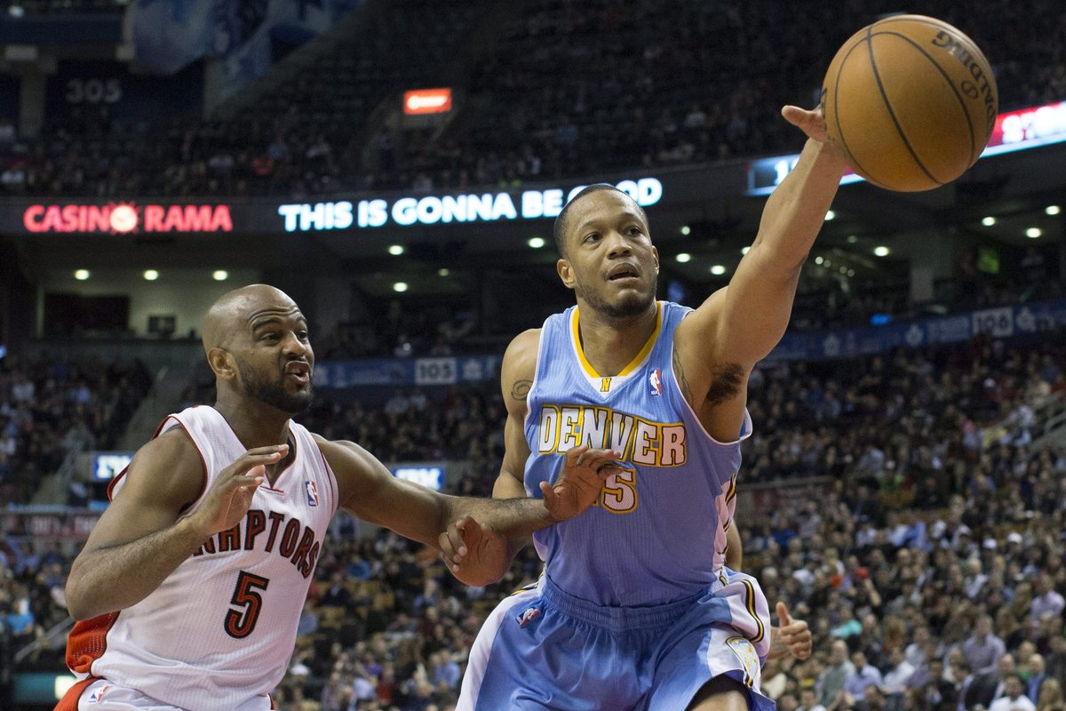 Denver Nuggets' Anthony Randolph reaches for the ball next to Toronto Raptors' John Lucas during the second half of an NBA ba