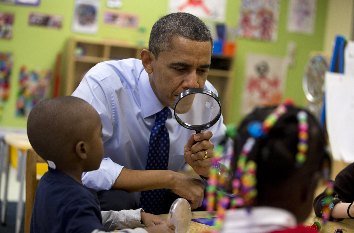 President Barack Obama looks through a magnifying glass during a learning game at a pre-kindergarten classroom at College Hei