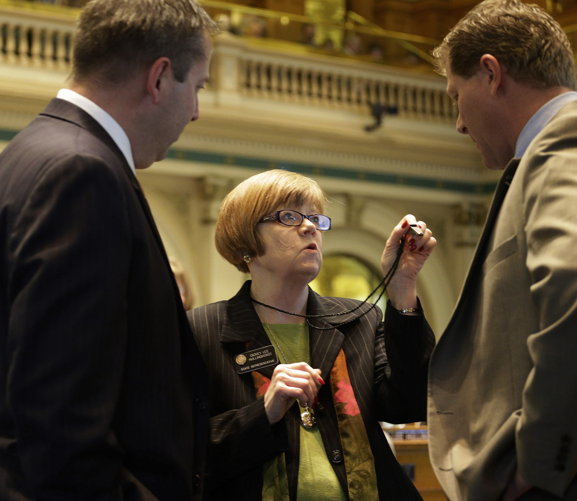 Rep. Dickey Lee Hullingworst, center, D-Boulder, shows House Minority Leader Mark Waller, left, R-Colorado Springs and Rep. B