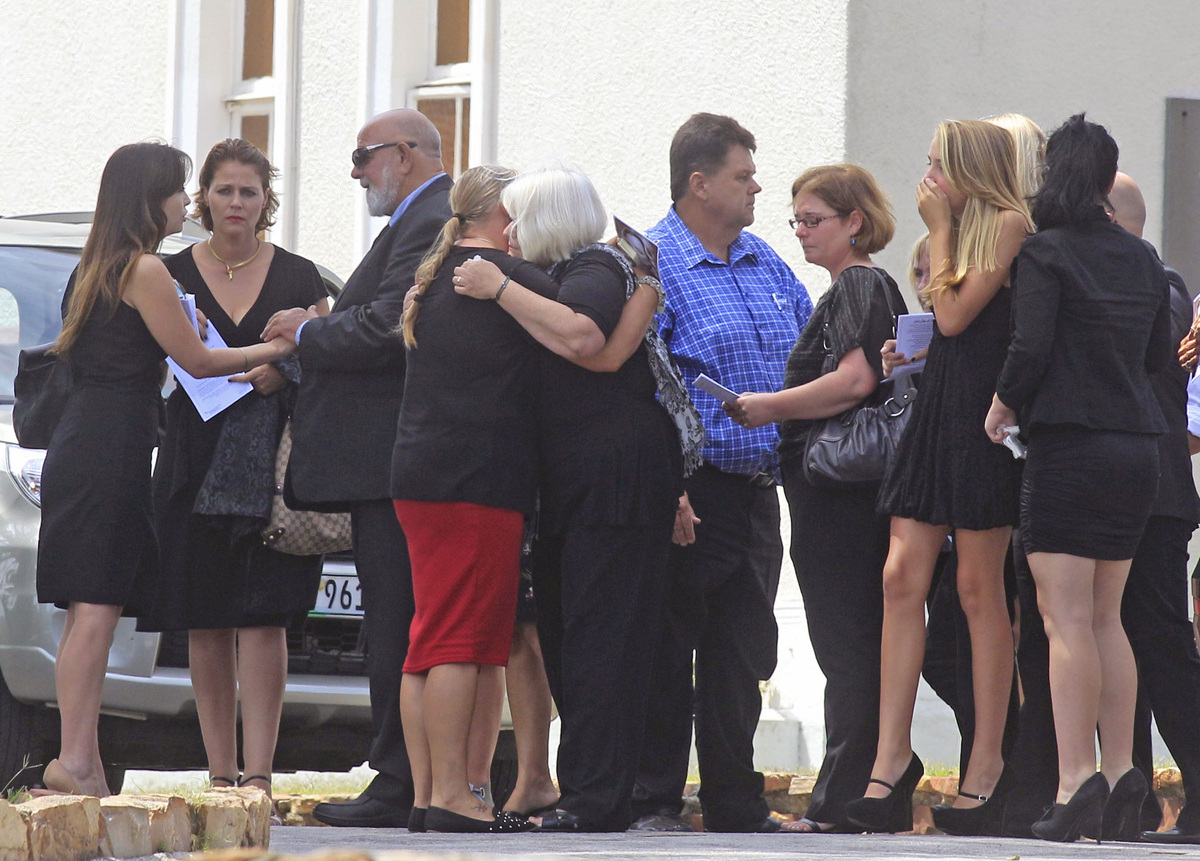 Barry Steenkamp, third left, the father of Reeva Steenkamp, greets people as he and others attend her funeral, in Port Elizab