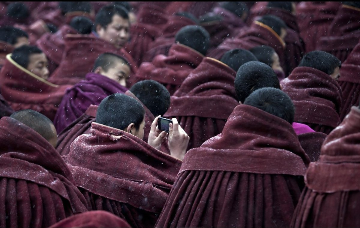 A monk consults his iPhone amid prayers at Labrang monastery, Xiahe, China. Communications technology and Buddhism have never