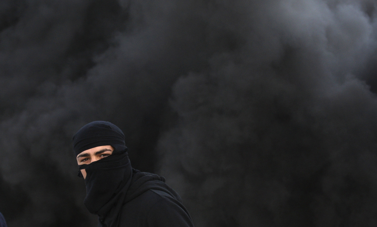 A Palestinian wears a mask during clashes with the Israeli army north of the West Bank city of Jenin in support to the Palest