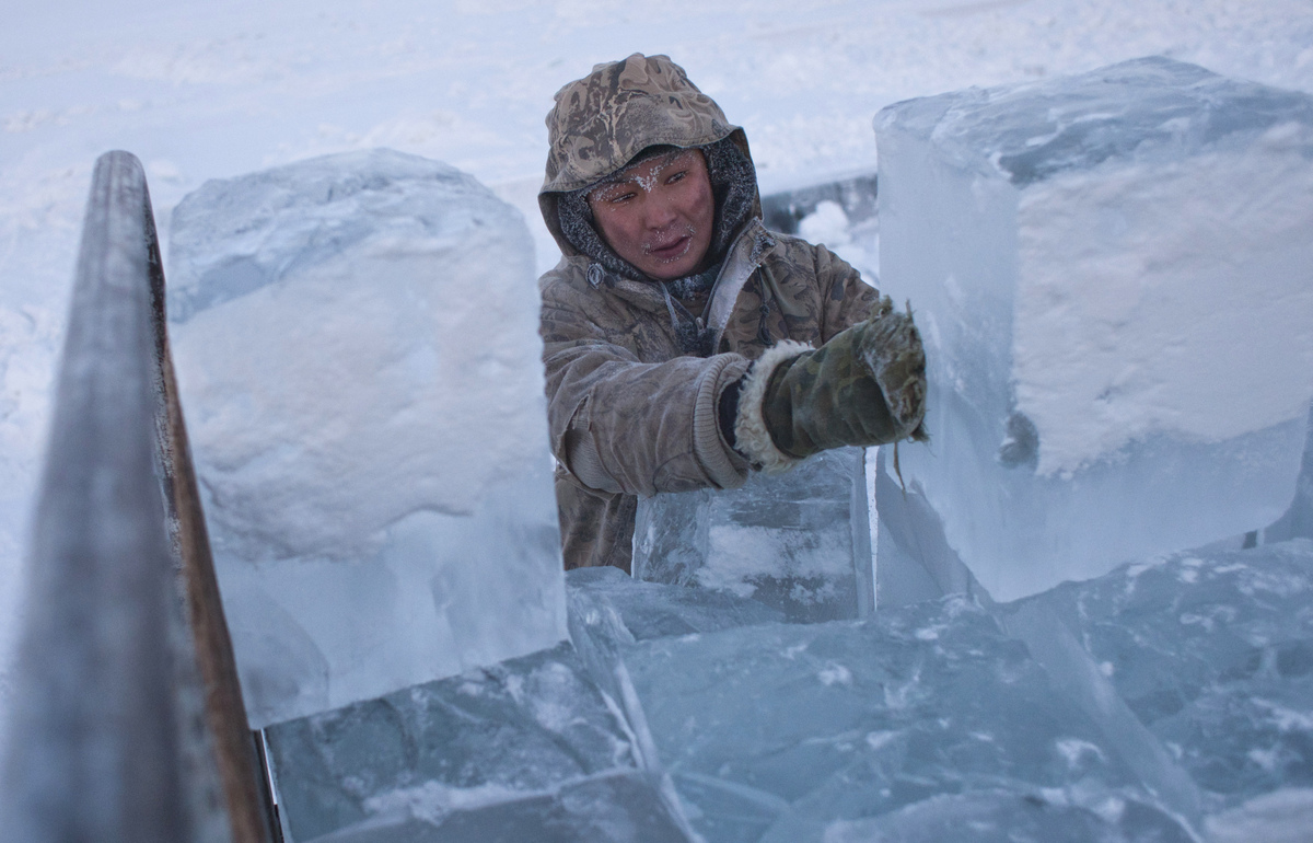 Ruslan, 35, loads blocks of ice onto a truck outside Yakutsk in the Republic of Sakha, northeast Russia, January 17, 2013. Th
