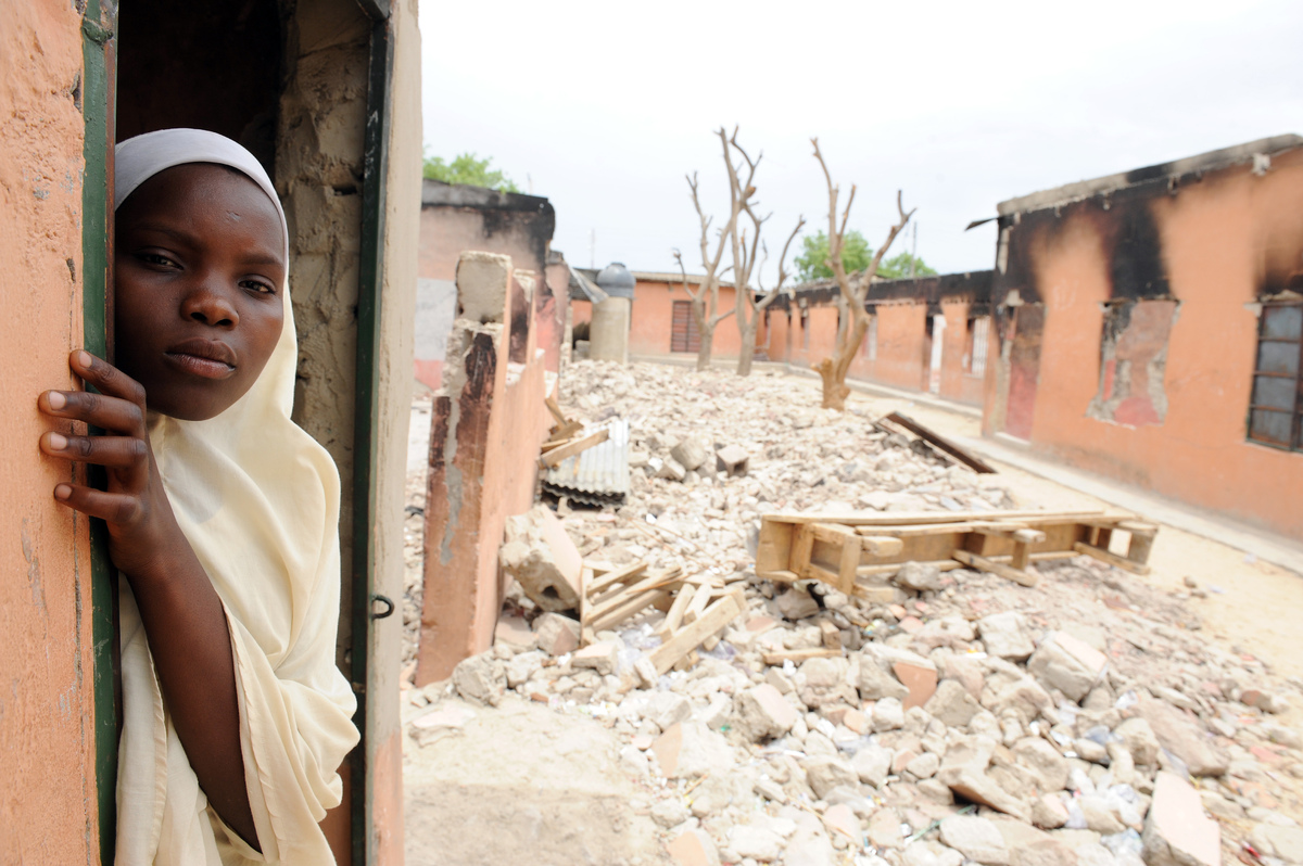 A female student stands in a burnt classroom at Maiduguri Experimental School, a private nursery, primary and secondary schoo