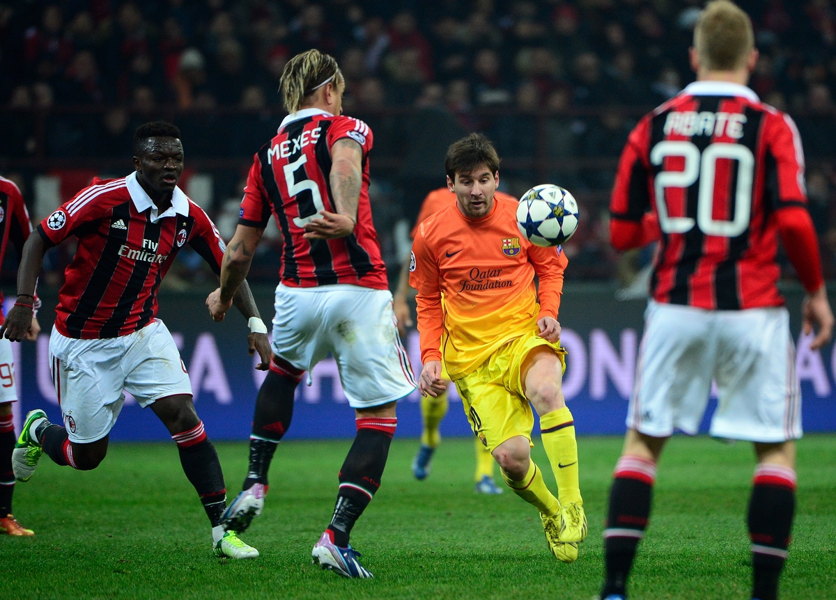 Barcelona's Argentinian forward Lionel Messi (L) fights for the ball with AC Milan's French defender Philippe Mexes during th