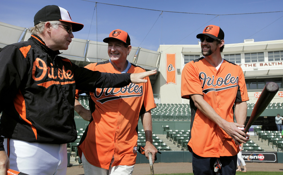 Baltimore Orioles manager Buck Showalter, left, talks with golf coach Hank Haney, center, and former Olympic swimmer Michael