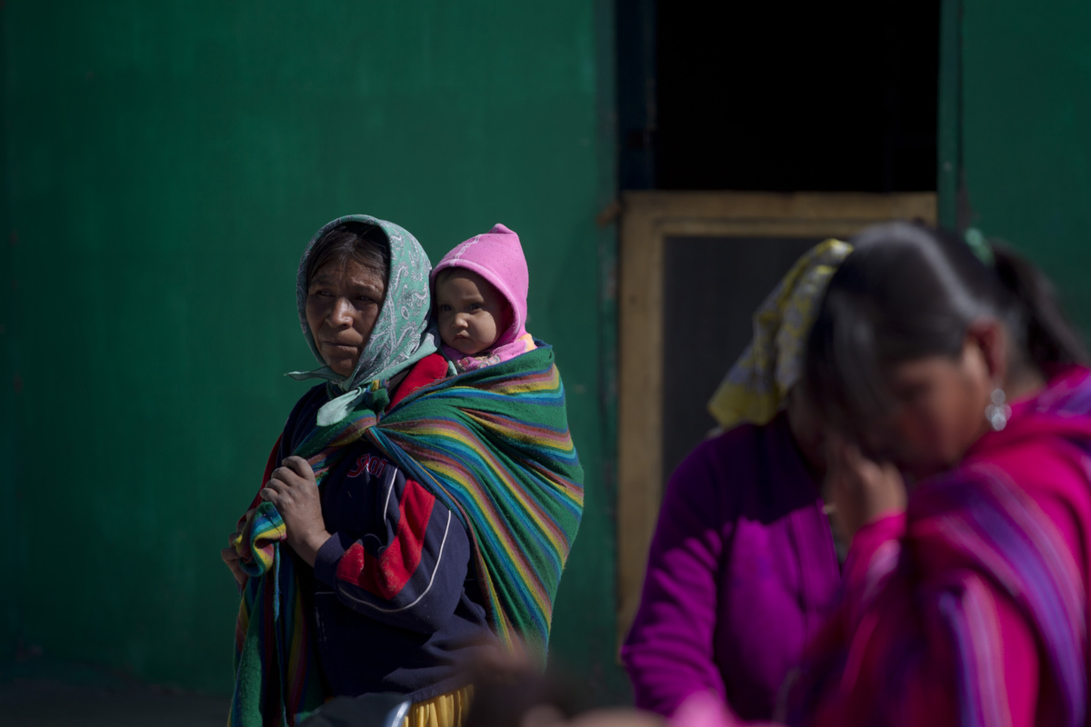 In this photo taken on Thursday Jan. 26, 2012, a Tarahumara Indian woman and her child watch as private aid is distributed in