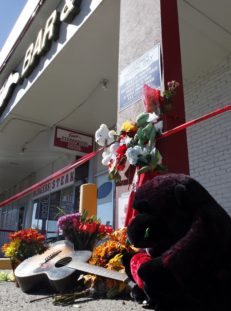 Flowers and stuffed animals are left at an informal memorial at Fero's Bar and Grill in Denver on Thursday, Oct. 18, 2012. Th