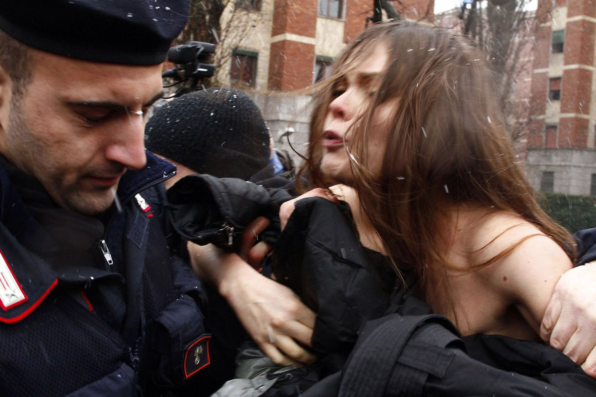 Police detain a woman protesting, as former Italian Premier Silvio Berlusconi voted, in Milan, Italy, Sunday, Feb. 24, 2013.