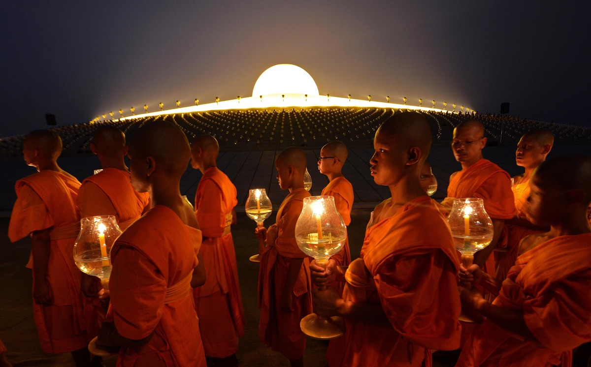 Buddhist monks hold candles as they walk around a Pagoda on Makha Bhucha Day at the Dhammakaya Temple in Pathumthani province