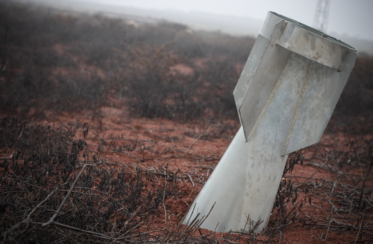 In this Sunday Jan. 6, 2013 photo, an unexploded ordinance lies half-buried in the ground on the frontline of the ongoing bat