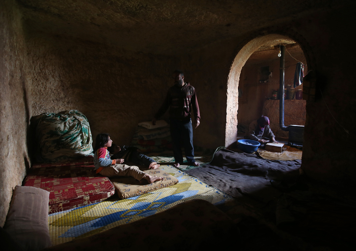 Sami, 32, center, speaks with his children at an underground Roman tomb which he uses with his family as shelter from Syrian