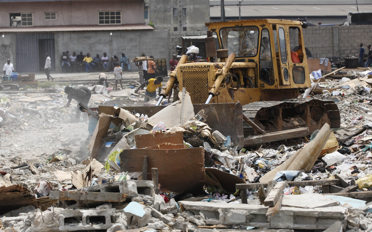 In this image taken Thursday Feb. 28, 2013 a bulldozer levels the site of demolished houses at Ijora Badia slum in Lagos, Nig