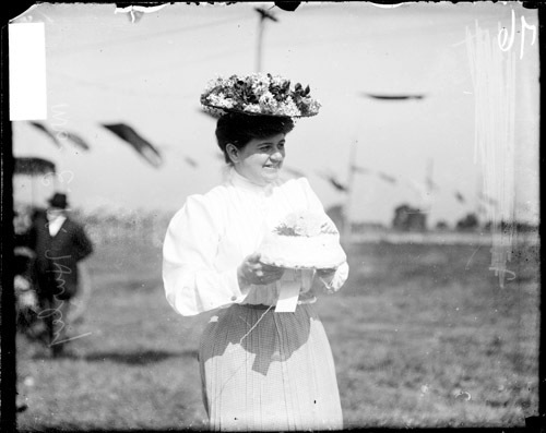 Mrs. E. N. Hurley carrying a cake on the grounds of the Wheaton Fair, 1907 (DN-0051894, Chicago Daily News negatives collecti