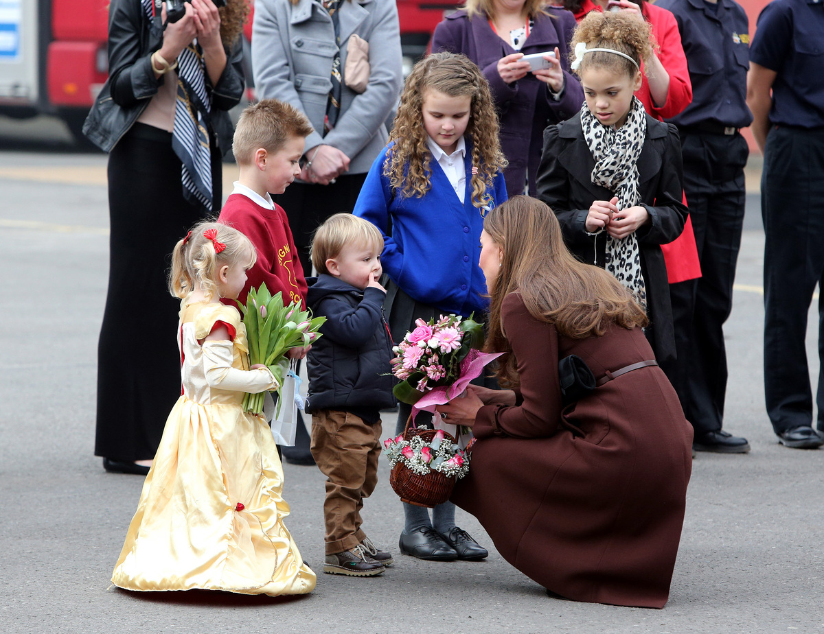 Britain's Kate, The Duchess of Cambridge, receives flowers from children during her visit to Humberside Fire and Rescue Servi