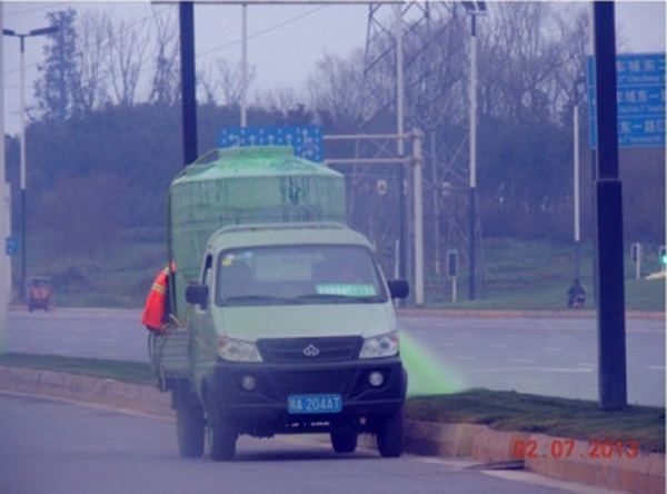 "Chinese workers spray ""Top Green"" dye on grass in Chengdhu."