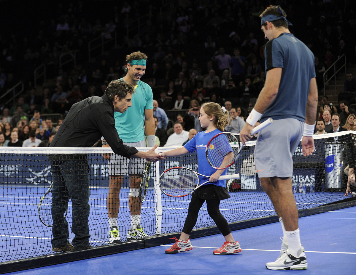 Actor Ben Stiller shakes hands with Rebecca Suarez, 9, of Huntington, N.Y. as Rafael Nadal, left, of Spain, and Juan Martin d