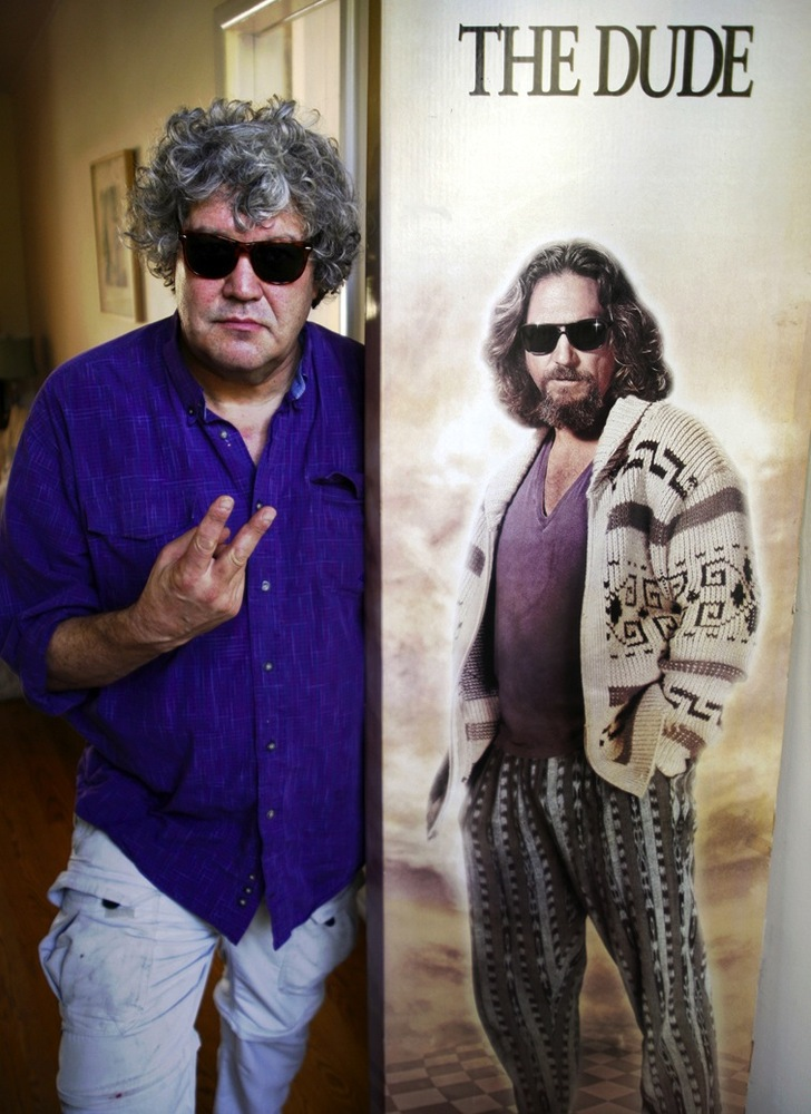 "Jeff Dowd poses with a poster for ""The Big Lebowski"""