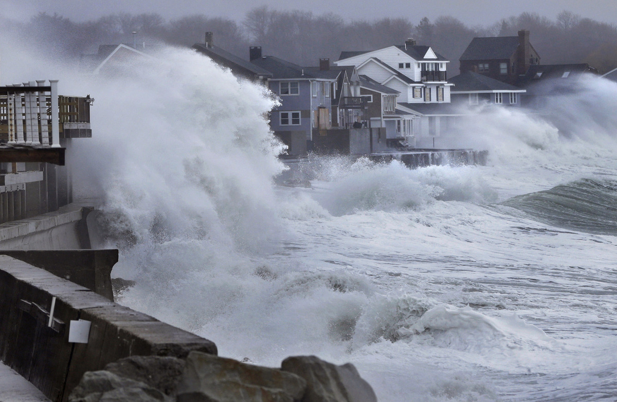 Ocean waves crash over a seawall and into houses along the coast in Scituate, Mass., Thursday, March 7, 2013. A nor'easter is