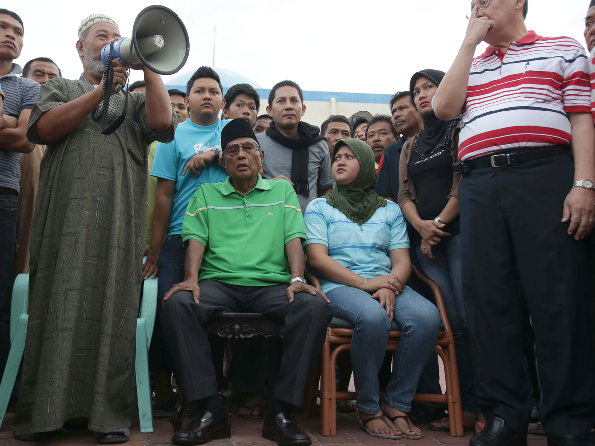Filipino Sultan Jamalul Kiram III, second from left, listens as supporters gather at the Blue Mosque at Maharlika village in