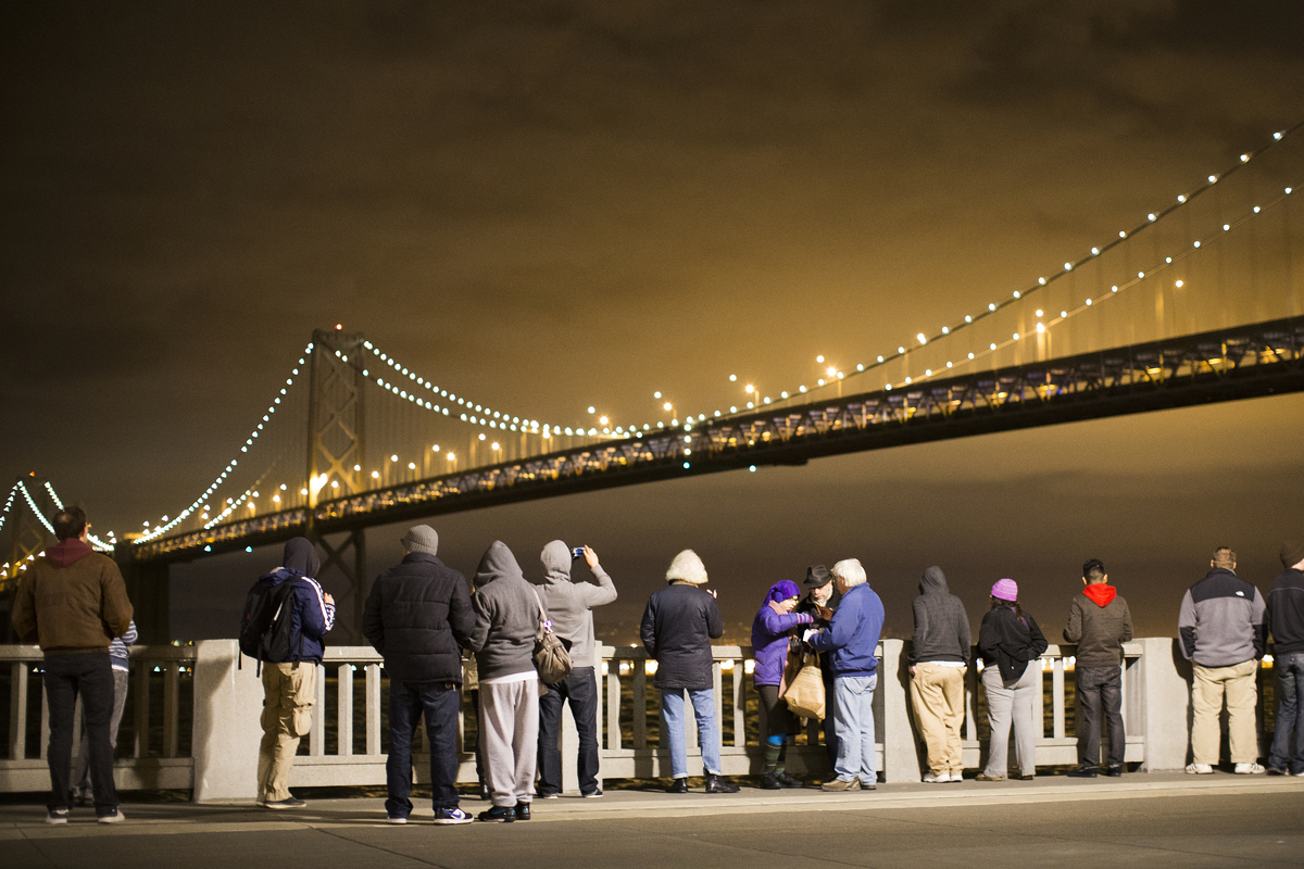 SAN FRANCISCO, CA - MARCH 5: A group of people watch the grand lighting of the Bay Lights art installation on the San Francis